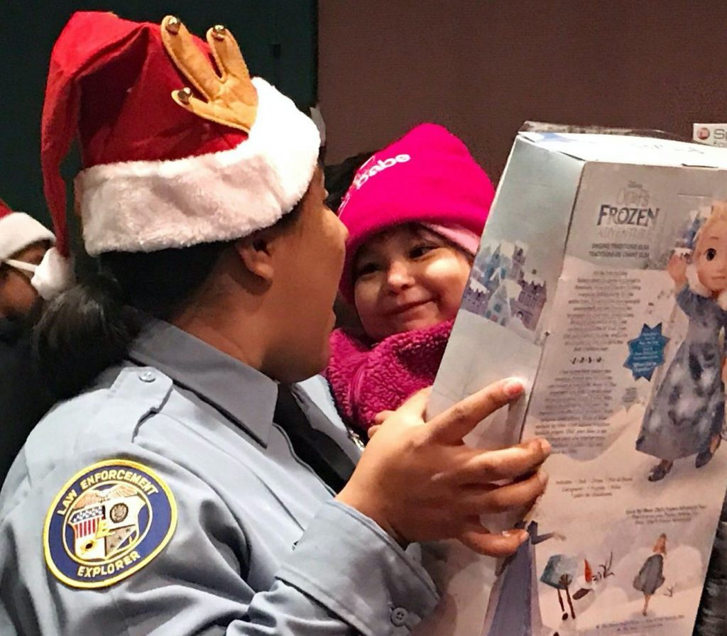 A police officer in a Santa hat giving a toy to a child