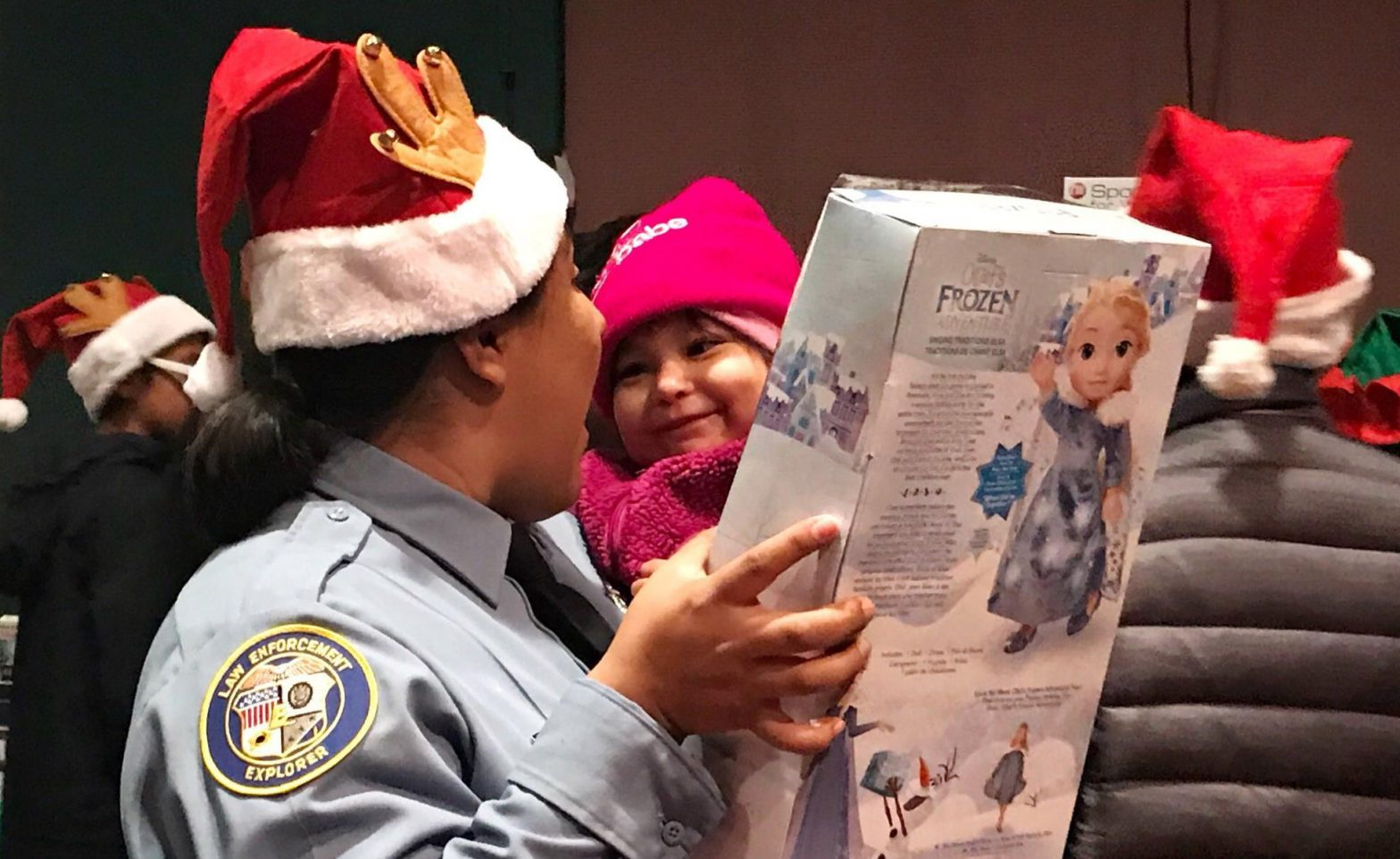 A police officer in a Santa hat sharing a toy with a child