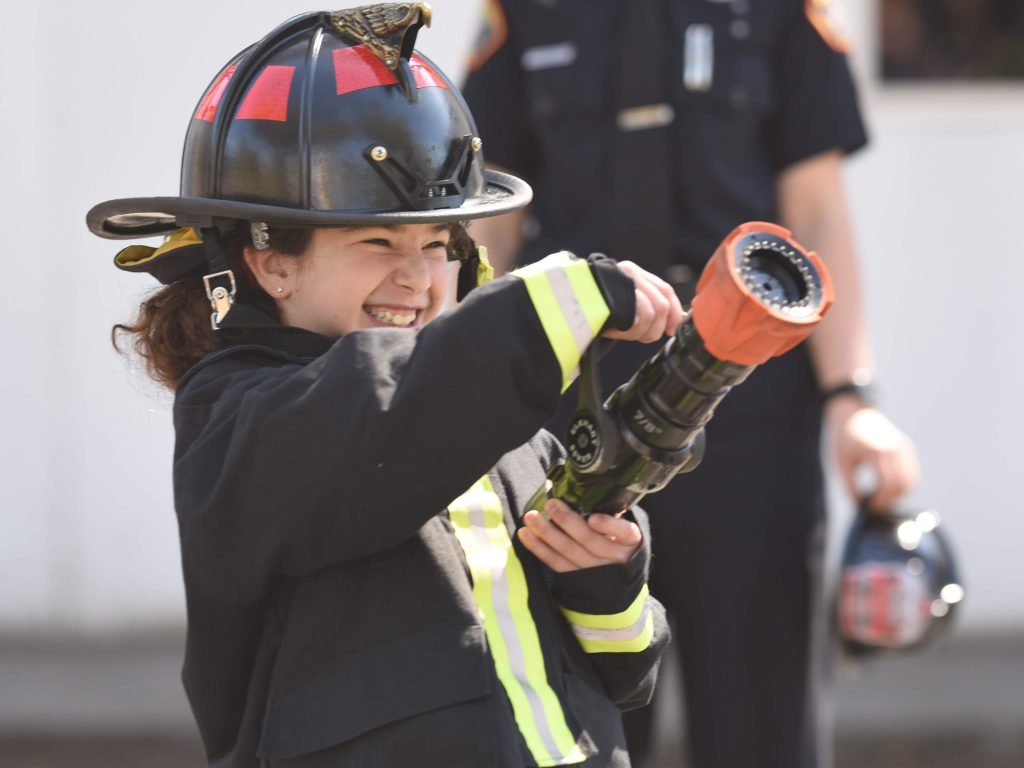 A young girl wearing a fire helmet and holding a hose, looking excited.