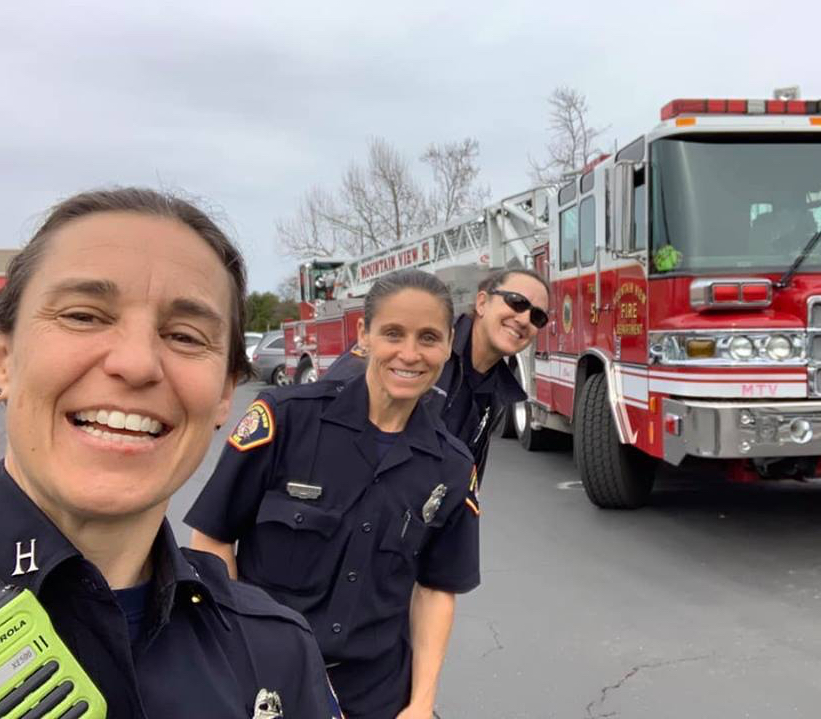 Three female firefighters smiling in front of a fire truck