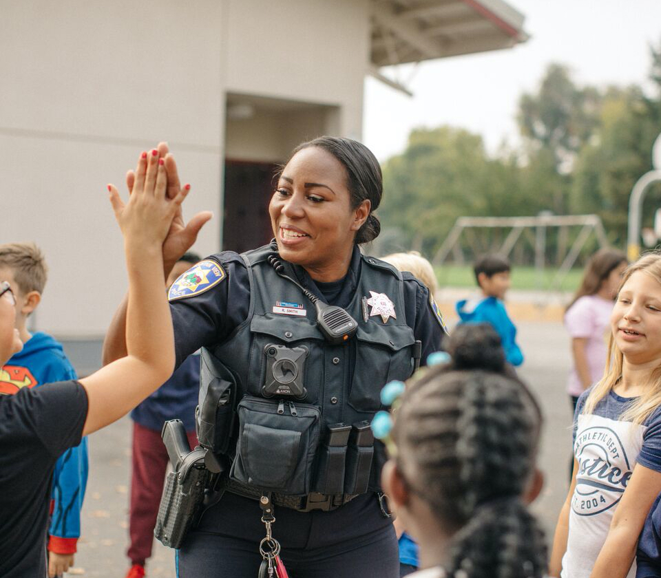 A MVPD PAL police officer smiling and high-fiving children during mentoring session